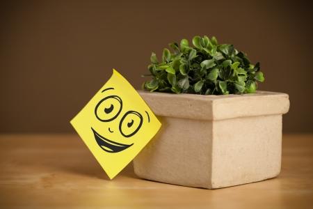cara sonriente dibujada en una nota pegada en una maceta fotos