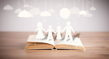 Cardboard figures of the family on opened book. The symbol of unity and happiness photo