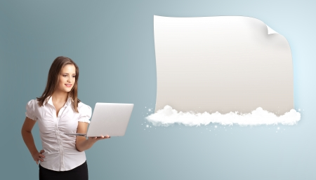 Attractive young woman holding a laptop and presenting modern copy space on clouds photo