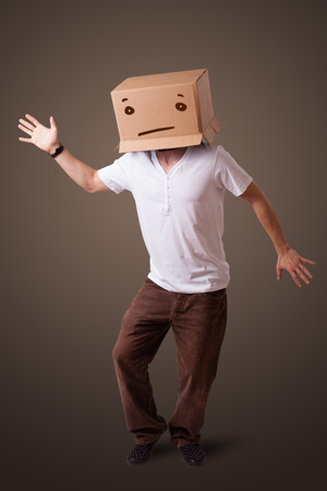 boxy: Young man standing and gesturing with a cardboard box on his head with straight face Stock Photo