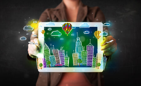 Young person showing tablet with hand drawn colorful cityscape photo