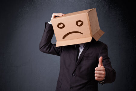 boxy: Businessman standing and gesturing with a cardboard box on his head with sad face