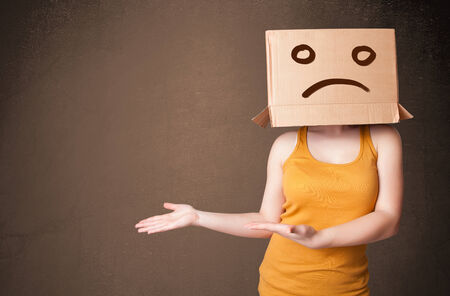 sad face: Young girl standing and gesturing with brown cardboard box on her head with sad face Stock Photo