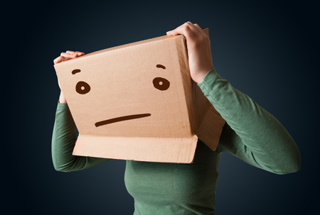hiding face: Young girl standing and gesturing with a cardboard box on her head with straight face