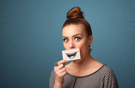 woman holding card: Happy cute girl holding paper with funny smiley drawing on gradient