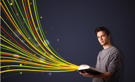 Young man reading a book while colorful lines are coming out of the book photo