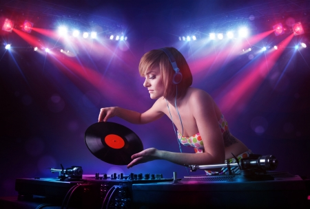Teenager Dj girl mixing records in front of a crowd on stage