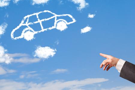 dream car: Mano que señala hacia a un coche nube en un cielo azul Foto de archivo