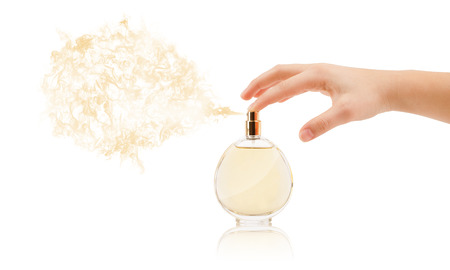 colored bottle: close up of woman hands spraying perfume
