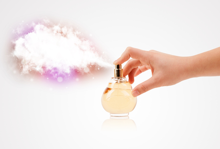 photomanipulation: close up of woman hands spraying colorful cloud from beautiful perfume bottle Stock Photo