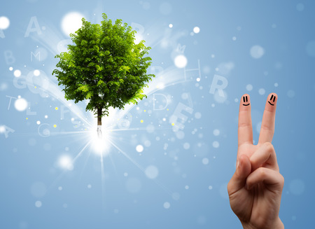 Happy finger smileys faces on hand with green magical glowing tree photo