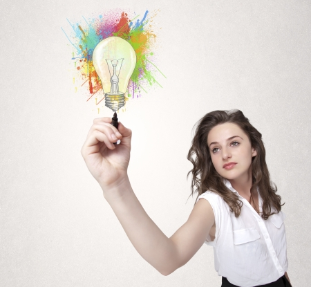 Young lady drawing a colorful light bulb with colorful splashes on white background photo