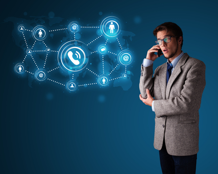 caller: Young boy standing and making phone call with social network icons Stock Photo