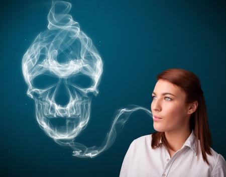 Pretty young woman smoking dangerous cigarette with toxic skull smoke Stock Photo - 25329910