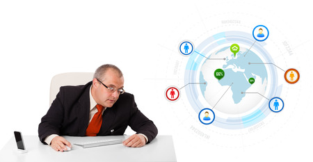 businessman sitting at desk with a globe and social icons, isolated on white photo