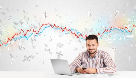 Business man sitting at table with stock market graph 3d letters Stock Photo - 25330169