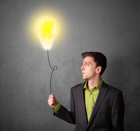 Young businessman holding a lightbulb balloon photo