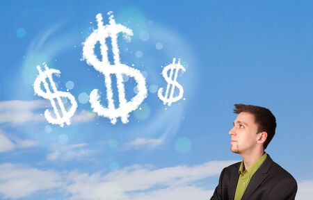 Businessman pointing at dollar sign clouds on blue sky concept photo