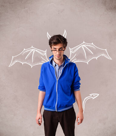 Young nasty man with devil horns and wings drawing photo