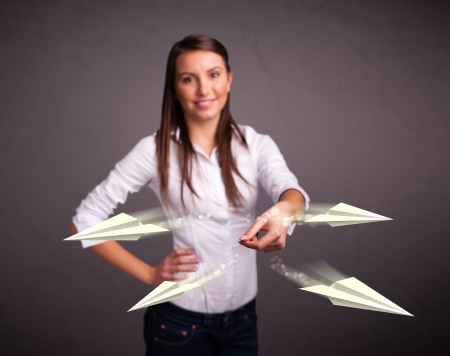 Beautiful young lady throwing origami airplanes photo