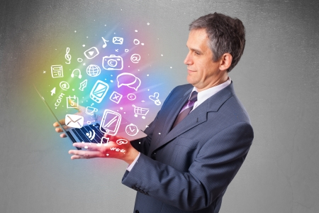 Middle aged businessman holding notebook with colorful hand drawn multimedia icons  photo