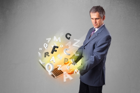 Middle aged businessman in suit holding laptop with colorful letters photo