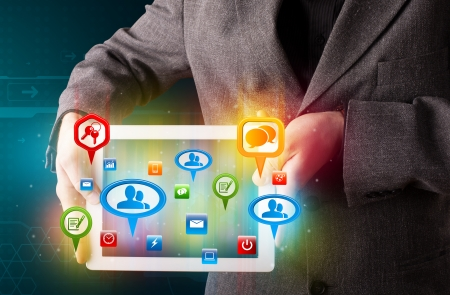Young businessman presenting modern tablet with colorful social signs and icons photo