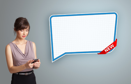 beautiful young woman holding a phone and presenting modern speech bubble copy space photo