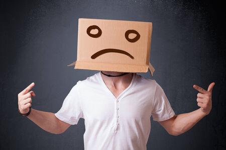 cara triste: Hombre joven de pie con una caja de cartón marrón en la cabeza con cara triste