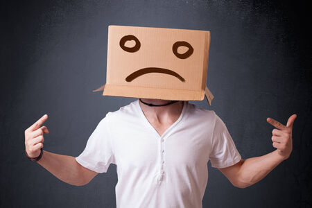 hiding face: Young man standing with a brown cardboard box on his head with sad face Stock Photo