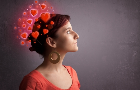 person thinking: Young person thinking about love with glowing red hearts  Banque d'images