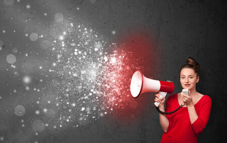 Woman shouting into megaphone and glowing energy particles explode concept photo