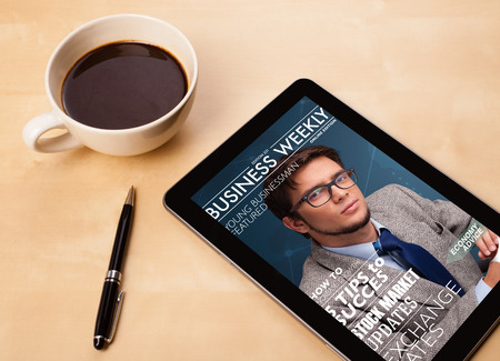 Workplace with tablet pc showing magazine cover and a cup of coffee on a wooden work table close-up photo