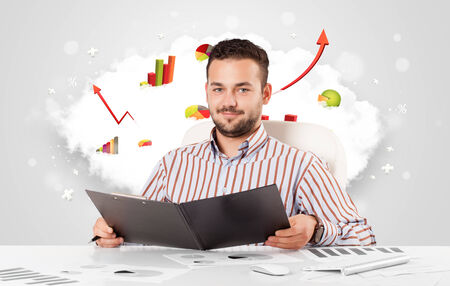 Handsome young businessman with cloud in the background containing colorful graphs and diagrams photo