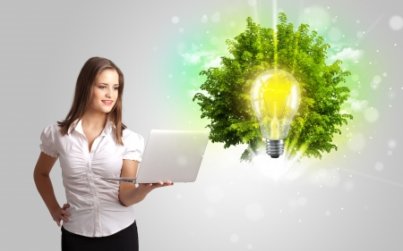 Young girl presenting idea light bulb with green tree concept photo