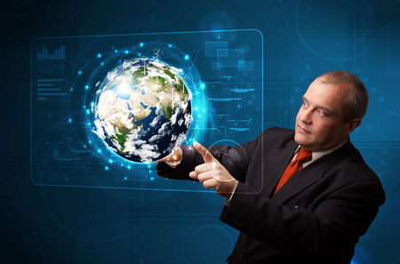 Businessman standing and touching high-tech 3d earth panel photo