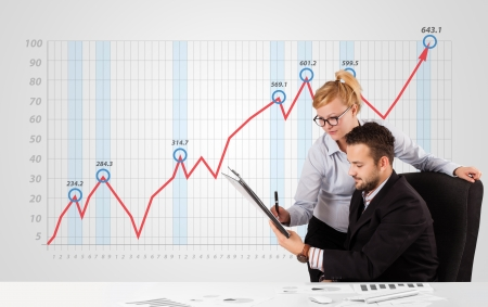 Young businessman and businesswoman calculating stock market with rising graph in the background photo