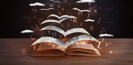 hardcover: Pages and glowing letters flying out of a book on wooden deck Stock Photo