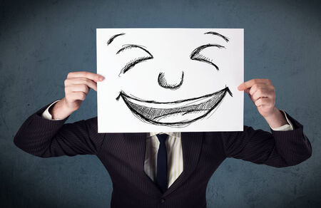 hiding face: Businessman holding a paper with a drawed smiley face on it in front of his head