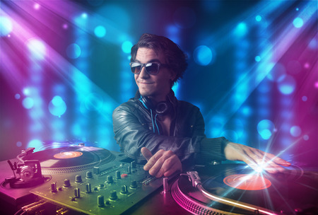 Young dj mixing music in a club with blue and purple lights photo