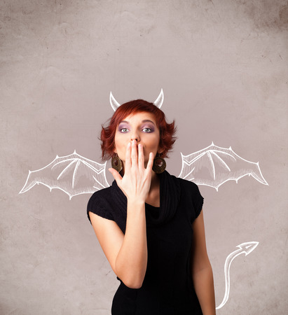naughty woman: Young nasty girl with devil horns and wings drawing Stock Photo