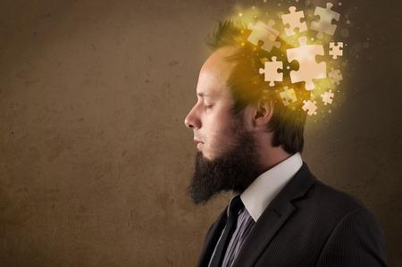 persona pensando: Persona joven que piensa con la mente rompecabezas brillante en la pared sucia Foto de archivo