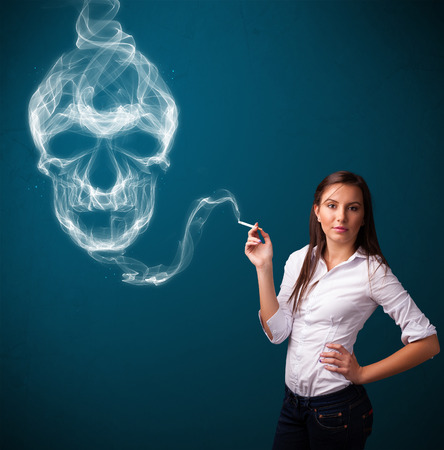 Pretty young woman smoking dangerous cigarette with toxic skull smoke Stock Photo - 25687921
