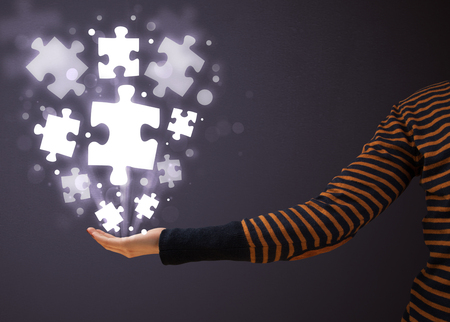 Woman holding shining puzzle pieces in her hand photo