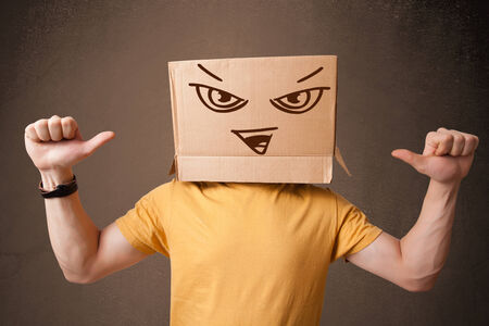 masquerader: Young man standing and gesturing with a cardboard box on his head with evil face