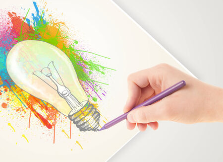 Hand drawing on a plain paper a colorful splatter lightbulb photo