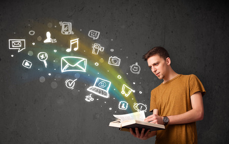 Young guy reading a book with multimedia icons coming out of the book photo