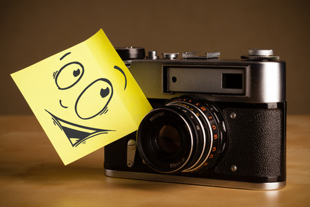 Drawn smiley face on a yellow note sticked on photo camera photo