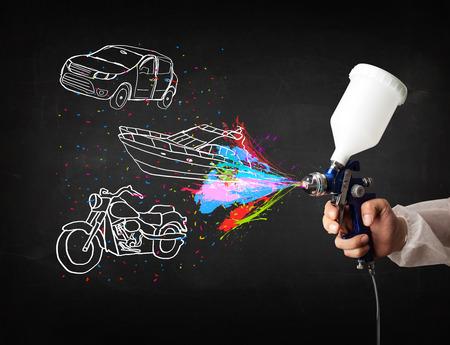 airbrushing: El hombre con la pintura de aerosol del aer�grafo con el coche, el barco y motocicleta dibujo sobre fondo oscuro