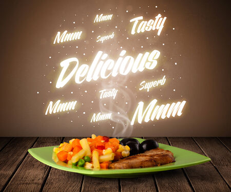 Food plate with delicious and tasty glowing writings on wood deck photo